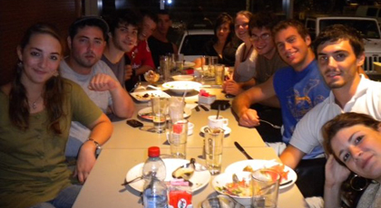 Summer uplan students sitting down to dinner in the ulpan club house.