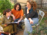 Bina students looking through a photo album of a young Israeli soldier